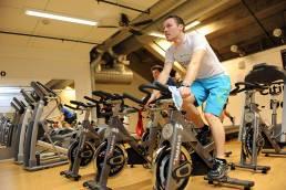 En mann trener utholdenhet på sykkel i Olympiaparken Sportssenter