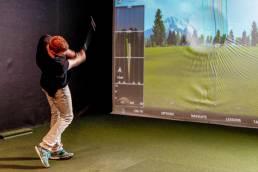 En mann spiller golf på golfsimulator