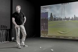 A man plays golf on simulator