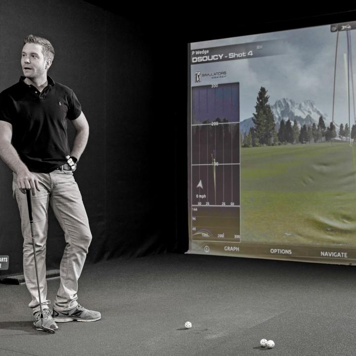 En mann spiller golf på simulator